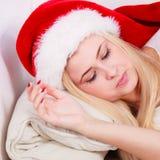 Γυναίκα στον ύπνο καπέλων Santa στον καναπέ Στοκ φωτογραφίες με δικαίωμα ελεύθερης χρήσης