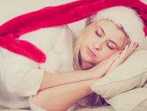 Γυναίκα στον ύπνο καπέλων Santa στον καναπέ Στοκ εικόνα με δικαίωμα ελεύθερης χρήσης