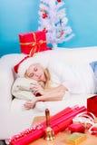 Γυναίκα στον ύπνο καπέλων Santa στον καναπέ Στοκ Εικόνες