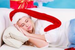 Γυναίκα στον ύπνο καπέλων Santa στον καναπέ Στοκ εικόνες με δικαίωμα ελεύθερης χρήσης