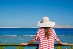 Γυναίκα στο άσπρο καπέλο που στέκεται δίπλα στο κιγκλίδωμα και τα βλέμματα εν πλω Στοκ Εικόνες