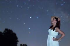 Γυναίκα στο άσπρο μακρύ φόρεμα κάτω από την έναστρη νύχτα Γυναίκα που κοιτάζει στην έναστρη νύχτα Γυναίκα κάτω από το νυχτερινό ο Στοκ Εικόνες