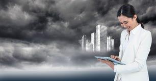 Γυναίκα στο άσπρο παλτό με την ταμπλέτα και το άσπρο κτήριο γραφικές ενάντια στο θυελλώδη ουρανό Στοκ Εικόνες