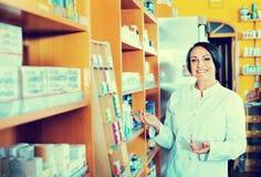 Γυναίκα στο άσπρο παλτό που προωθεί τα συμπληρώματα υγείας στο φαρμακείο στοκ εικόνες