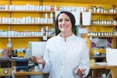 Γυναίκα στο άσπρο παλτό που προωθεί τα συμπληρώματα υγείας στο φαρμακείο στοκ φωτογραφία