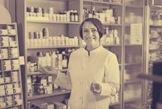 Γυναίκα στο άσπρο παλτό που προωθεί τα συμπληρώματα υγείας στο φαρμακείο στοκ εικόνα