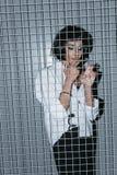 Γυναίκα στο άσπρο πουκάμισο και μανσέτες που καπνίζουν το τσιγάρο πίσω από τη σχάρα Στοκ εικόνες με δικαίωμα ελεύθερης χρήσης