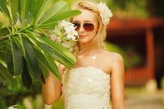 Γυναίκα στο άσπρο φόρεμα με το plumeria στο πρόσωπό της όμορφο κορίτσι στο τροπικό δέντρο Στοκ Εικόνες