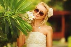 Γυναίκα στο άσπρο φόρεμα με το plumeria στο πρόσωπό της όμορφο κορίτσι στο τροπικό δέντρο Στοκ εικόνες με δικαίωμα ελεύθερης χρήσης