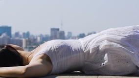 Γυναίκα στο άσπρο φόρεμα που βρίσκεται στη εικονική παράσταση πόλης προσοχής στεγών, χαλαρώνοντας παράτολμος απόθεμα βίντεο