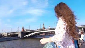Γυναίκα στο άσπρο φόρεμα που εξετάζει τη Μόσχα Κρεμλίνο από τη βάρκα γύρου ποταμών απόθεμα βίντεο