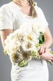 Γυναίκα στο άσπρο φόρεμα που κρατά μια ανθοδέσμη στοκ εικόνα