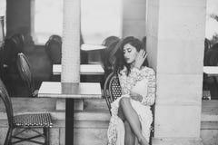 Γυναίκα στο άσπρο φόρεμα υπαίθριο Η προκλητική γυναίκα κάθεται μόνο στον καφέ οδών Το πρότυπο μόδας με τη γοητεία κοιτάζει και ma στοκ φωτογραφία με δικαίωμα ελεύθερης χρήσης
