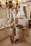 Γυναίκα στο αδιάβροχο μετά από το κόμμα στο σπίτι στην κουζίνα Έβγαλε τα παπούτσια της ουίσκυ γυαλιού Στοκ φωτογραφία με δικαίωμα ελεύθερης χρήσης