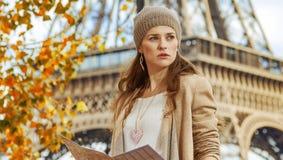 Γυναίκα στο ανάχωμα στο Παρίσι με το χάρτη που εξετάζει την απόσταση Στοκ Εικόνα