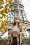 Γυναίκα στο ανάχωμα στο Παρίσι με το χάρτη που εξετάζει την απόσταση Στοκ εικόνες με δικαίωμα ελεύθερης χρήσης