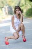 Γυναίκα στο απότομα άσπρο φόρεμα και τα κόκκινα υψηλά τακούνια στοκ εικόνες