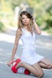 Γυναίκα στο απότομα άσπρο φόρεμα και τα κόκκινα υψηλά τακούνια στοκ φωτογραφία με δικαίωμα ελεύθερης χρήσης