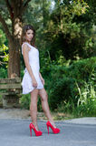Γυναίκα στο απότομα άσπρο φόρεμα, πολύβλαστη βλάστηση ως υπόβαθρο στοκ εικόνες