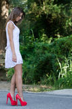 Γυναίκα στο απότομα άσπρο φόρεμα, πολύβλαστη βλάστηση ως υπόβαθρο στοκ φωτογραφία
