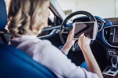 Γυναίκα στο αυτοκίνητο που χρησιμοποιεί την ψηφιακή ταμπλέτα στοκ εικόνες