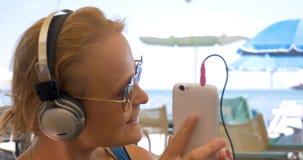 Γυναίκα στο βίντεο κασκών που κουβεντιάζει σε κινητό απόθεμα βίντεο
