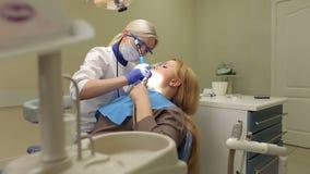 Γυναίκα στο γραφείο οδοντιάτρων, καθαρισμός δοντιών απόθεμα βίντεο