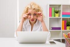 Γυναίκα στο γραφείο που εξετάζει τον υπολογιστή και που κρατά τα μάτια της ανοικτά Στοκ Εικόνα