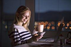 Γυναίκα στο γραφείο, που κρατά το smartphone, που λειτουργεί στο lap-top τη νύχτα Στοκ Εικόνα