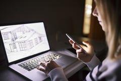 Γυναίκα στο γραφείο, που κρατά το smartphone, που λειτουργεί στο lap-top τη νύχτα Στοκ φωτογραφία με δικαίωμα ελεύθερης χρήσης