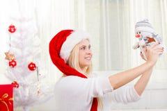 Γυναίκα στο δώρο εκμετάλλευσης καπέλων Santa, διακόσμηση χιονανθρώπων Στοκ Εικόνες