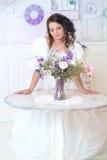 Γυναίκα στο εκλεκτής ποιότητας φόρεμα πολυτέλειας που στέκεται στο φωτεινό δωμάτιο Στοκ Φωτογραφία