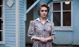 Γυναίκα στο εκλεκτής ποιότητας φόρεμα σε ένα υπόβαθρο ενός ξύλινου σπιτιού Στοκ Εικόνες