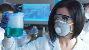 Γυναίκα στο εργαστήριο που λειτουργεί με τις χημικές ουσίες απόθεμα βίντεο