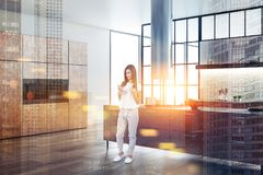 Γυναίκα στο εσωτερικό καφετί countertops κουζινών διπλάσιο στοκ εικόνες