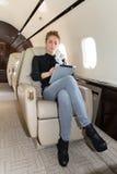 Γυναίκα στο εταιρικό αεριωθούμενο αεροπλάνο που εξετάζει τον υπολογιστή ταμπλετών Στοκ Εικόνες