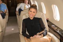 Γυναίκα στο εταιρικό αεριωθούμενο αεροπλάνο που χαμογελά στη κάμερα Στοκ φωτογραφία με δικαίωμα ελεύθερης χρήσης