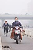 Γυναίκα στο ε-ποδήλατο καλμένη στην αιθαλομίχλη πόλη, Πεκίνο, Κίνα στοκ εικόνα με δικαίωμα ελεύθερης χρήσης