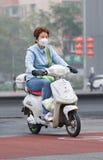 Γυναίκα στο ε-ποδήλατο καλμένη στην αιθαλομίχλη πόλη, Πεκίνο, Κίνα στοκ εικόνες με δικαίωμα ελεύθερης χρήσης