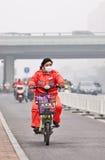 Γυναίκα στο ε-ποδήλατο καλμένη στην αιθαλομίχλη πόλη, Πεκίνο, Κίνα Στοκ Εικόνες