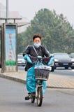 Γυναίκα στο ε-ποδήλατο καλμένη στην αιθαλομίχλη πόλη, Πεκίνο, Κίνα στοκ φωτογραφία