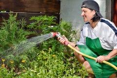 Γυναίκα στο θερινό εξοχικό σπίτι polivat Στοκ φωτογραφία με δικαίωμα ελεύθερης χρήσης