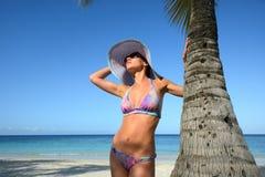 Γυναίκα στο θερινό καπέλο που κάνει ηλιοθεραπεία κάτω από έναν φοίνικα σε μια ανασκόπηση Στοκ Φωτογραφία