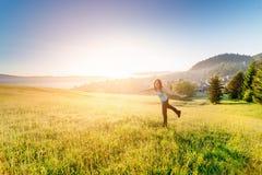 Γυναίκα στο θερινό λιβάδι που απολαμβάνει το πρωί ομορφιάς στο βουνό στοκ εικόνα