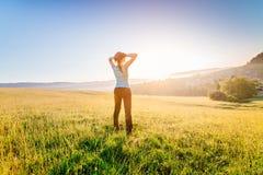 Γυναίκα στο θερινό λιβάδι που απολαμβάνει το πρωί ομορφιάς στο βουνό στοκ φωτογραφία με δικαίωμα ελεύθερης χρήσης