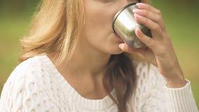 Γυναίκα στο θερμαίνοντας θερμαμένο κρασί κατανάλωσης πουλόβερ, καυτό ποτό, καιρός φθινοπώρου απόθεμα βίντεο
