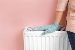 Γυναίκα στο θερμαίνοντας χέρι γαντιών στη θέρμανση του θερμαντικού σώματος κοντά στον τοίχο χρώματος στοκ εικόνα με δικαίωμα ελεύθερης χρήσης