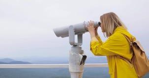 Γυναίκα στο κίτρινο αδιάβροχο που εξετάζει μέσω των διοπτρών τουριστών τα βουνά απόθεμα βίντεο