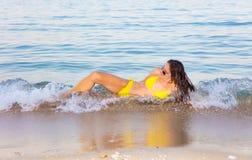 Γυναίκα στο κίτρινο μπικίνι στην παραλία στοκ εικόνα