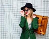 Γυναίκα στο καπέλο και πράσινος επενδύτης στο ύφος της δεκαετίας του '90 με τη βαλίτσα ταξιδιού στοκ φωτογραφίες με δικαίωμα ελεύθερης χρήσης